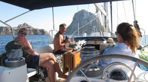 Una familia se encuentra a bordo de un velero. De fondo puede advertirse Es Vedrà. El hombre mantiene en sus manos unos prismáticos.