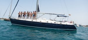 Un grupo de amigos posan en la cubierta de un velero. Todos parecen mostrar divertirse.