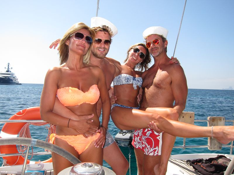 Two couples pose in their Ibiza boat charter in a fun way. The boys are wearing sea hats.