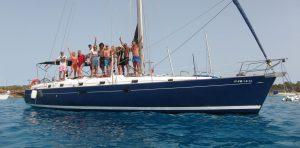 Un grupo de amigos disfruta de su alquiler de veleros y posa de manera divertida en la cubierta del barco.