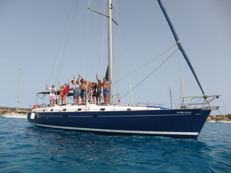 Group of friends posing on the deck of their sailing boat Ibiza