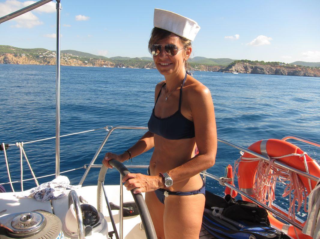 Alessandra con un gorro marinero llevando el timón