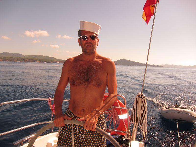 Giampaolo con un gorro marinero llevando el timón