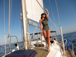 Alquiler barco Formentera pose modelos: una bella modelo posa en la cubierta de nuestro velero mientras navegamos. La modelo lleva un traje de baño color verde. En la cabeza, una gorra