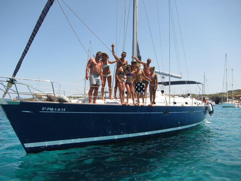 Una familia disfruta de su alquiler de barco en Ibiza con patrón. Varios adultos acompañados de varios niños posan de manera divertida en la cubierta del velero.