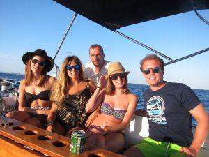 Tres chicas y dos chicos se muestran sentados en la cubierta de su alquiler de barcos con patrón Ibiza