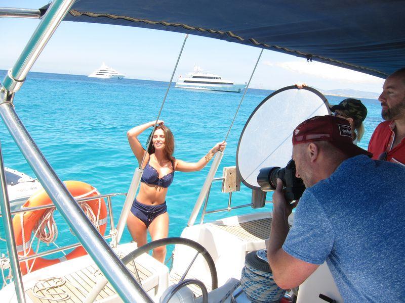 Alquiler de barcos en Formentera modelo: en la imagen puede apreciarse a un fotógrafo dirigiendo a su equipo de iluminación para obtener la mejor fotografía de una bella modelo. Destacan los bellos contrastes de azules y verdes