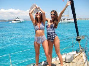 Alquiler de barcos en Ibiza sesión fotos: las dos bellas modelos posan de manera divertida en la proa de la embarcación luciendo elegantes trajes de baño