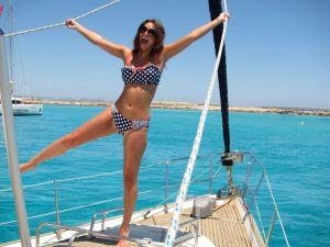 Alquiler de veleros en Ibiza pose modelos: una modelo en biquini posa de manera divertida agarrada a las dos escotas de la vela génova
