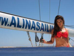 Bella modelo de alquiler velero Ibiza modelos posa frente a la botavara de nuestro velero. La modelo lleva un bonito biquini rojo