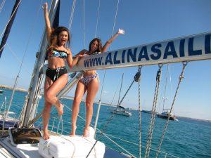 Dos bellas modelos de alquiler velero Ibiza pose modelos posan alegremente junto a la botavara de nuestro magnífico velero. De fondo, las prístinas aguas turquesas de Formentera