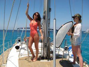 Bella modelo en nuestro alquiler velero Ibiza sesión fotos posando en la cubierta de nuestra embarcación. Una técnico en iluminación consigue la mejor iluminación para obtener una fotografía perfecta