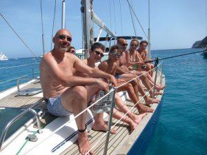 Una familia con niños disfruta de sus vacaciones de alquiler veleros Ibiza. Aparecen sentados en la banda de babor de un velero. Una mujer está pescando con una caña de pescar.