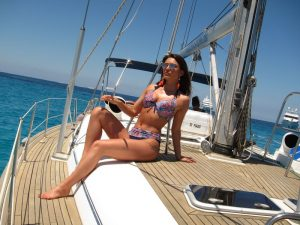 Alquiler veleros Ibiza sesión fotos. Una bella modelo posa en la cubierta de un velero. De fondo, las bellas aguas de Formentera