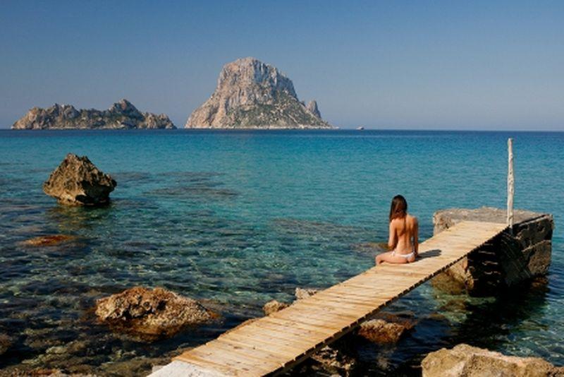 Las excursiones barco en Ibiza te trasladarán a lugares de incomparable belleza. En la imagen vemos a una joven disfrutando de las bellas vistas de Es Vedrà