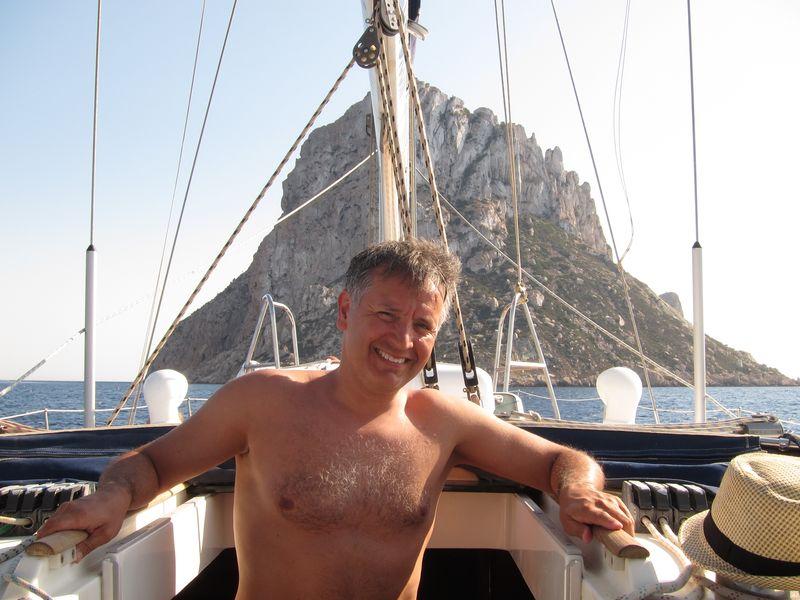 Nuestras excursiones barco Ibiza están llenas de clientes satisfechos. En la imagen se muestra a un cliente sonriente con el islote de Es Vedrà de fondo