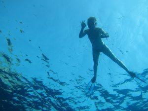 Las excursiones en barco Ibiza a Saona ofrecen aguas de una transparencia incomparable. En la imagen podemos apreciar a una joven practicando snorkel flotando en la superficie y haciendo la señal de OK