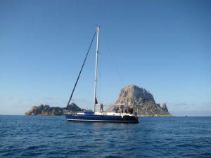 Magnífica Ibiza boat trips en los islotes de Es Vedrà y Es Vedranel. En la imagen puede apreciarse un bello belero de casco azul con los islotes de fondo
