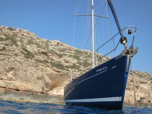Ibiza boat trips caves: in the picture you can see a sailing boat anchored inf front of a cliff