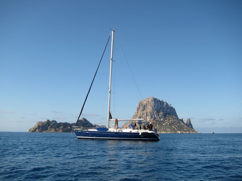Magnífica Ibiza boat trips en los islotes de Es Vedrà y Es Vedranell. En la imagen puede apreciarse un bello velero de casco azul con los islotes de fondo