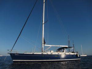 Obtendrás tu licencia navegación náutica en nuestro barco escuela. Nuestro barco escuela es un velero de casco azul de diez y seis metros de eslora y cinco camarotes. En la imagen podemos ver nuestro velero de casco azul fondeado en el mar.