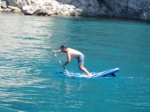 Grupo de Sevillanos alquiler de veleros con patrón en Ibiza. Gonzalo practicando paddle surf