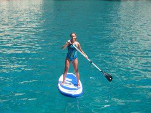 Grupo sevillanos alquiler veleros con patrón en Ibiza. María demostrando su destreza con el paddle surf