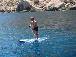 Grupo sevillanos alquiler veleros Ibiza. Nonin demostrando sus destrezas con el paddle surf