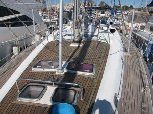 En la foto puede advertirse la cubierta de teca alquiler velero con patrón Ibiza. La parte superior ha sido tratada con un sellante. La parte inferior ha sido limpiada y abrillantada. La parte inferior es de un color más gris que la parte superior