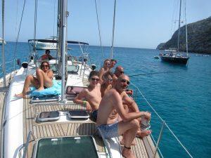 Un grupo disfruta de sus vacaciones en familia velero Ibiza. Algunos de ellos pescan y otros toman el sol en cubierta.
