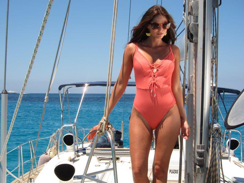 Bella modelo posa en cubierta de Ibiza boat charter models. La modelo lleva un atractivo traje de baño color salmón